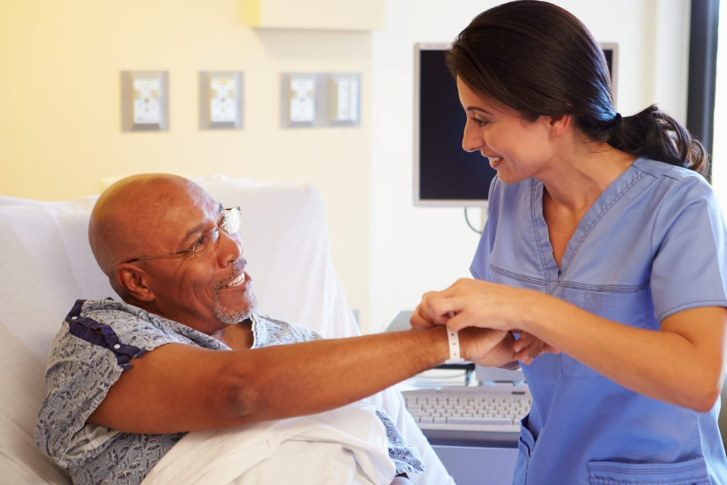 Man in Hospital receiving a Wristband