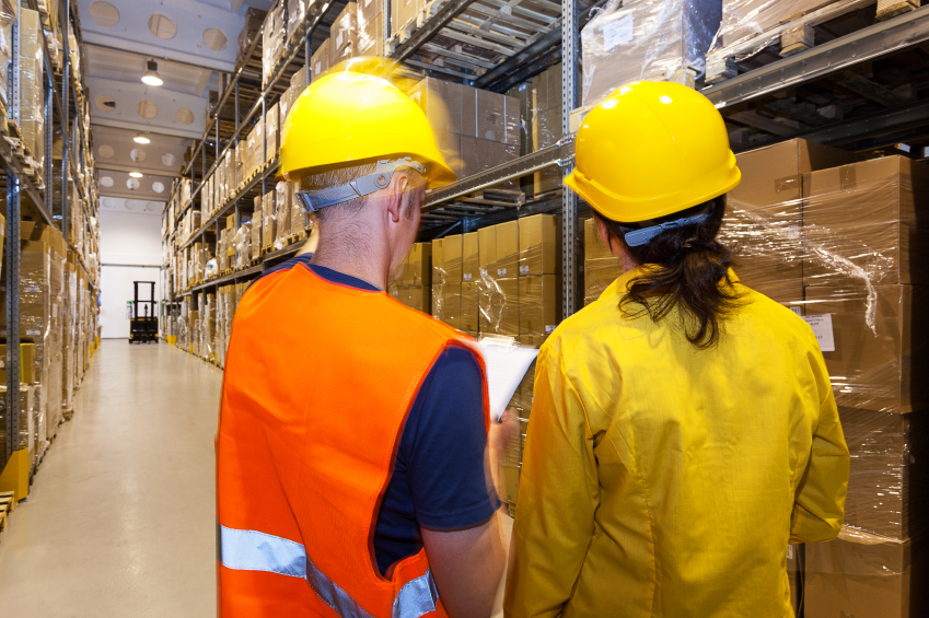 Manager and worker in warehouse with stillage