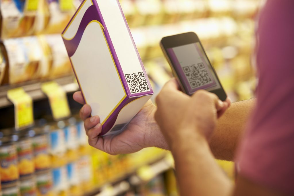 Man Scanning QR Code In Supermarket With Mobile Phone
