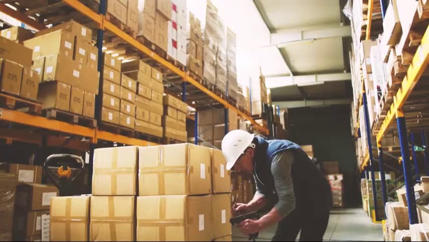 Man scanning boxes in warehouse